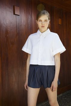 - Collared shirt with cuffed sleeves, boxy fit and cropped length. - 4mm thick white Australian mother-of-pearl buttons. - Signature pleated one-piece back. The debut UNIFORME shirt collection feature