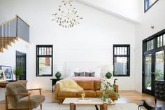 Where white walls and black trim make this loft-style master suite from PRAIRIE feel chic and contemporary, a mix of furniture and throws warm the interior and give it a comfortable, collected look.
