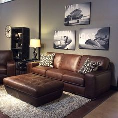 Family Room With Warm Gray Walls, Black And White Art, Brown Leather  Furniture, Ottoman, Airplane Canvas Art