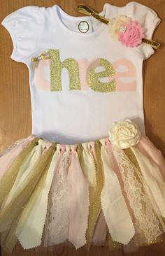 A scrap fabric and tulle tutu outfit in a pink, gold, and ivory third birthday three theme. The outfit includes the tutu with lace accents, a
