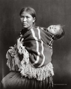 Navajo Indian woman carrying sleeping child on back. United States ...