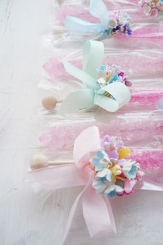 Pink rock candy with millinery flowers - such a pretty favor!