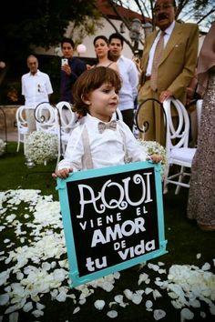 Paje de boda con letrero para la entrada de la novia en una boda al aire libre.
