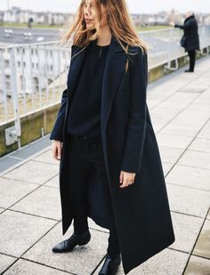 black chunky sweater with black wool coat and black boots