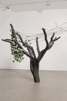 """""""Who can I turn to if I turn away"""", 2005 // The middle room displays a big dark tree with sturdy branches and a series of ceramic apples hanging down on black ropes from one branch. This bronze tree with the title who can I turn to if you turn away is a cast of a tree that Gallaccio found in California, having fallen victim to woodpeckers. The woodpecker's tracks were used to thread the ropes with apples."""