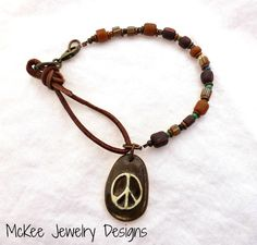 Leather, Indonesian glass and ceramic peace sign charm bracelet.