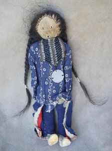 Rare Northern Cheyenne cradleboard with male doll, circa 1880. In classic Northern Cheyenne colors of white, blue and red, the cradle has dentalia drops with red white-heart pony beads. It retains what appear to be its original sticks.