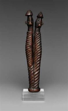 A YAKA CHARM FIGURE  Mbwoolo, the spirally carved forked body terminating in two heads, each with conical headgear, pierced below the necks, dark glossy patina.   22 cm. long