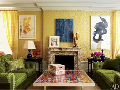 Walls upholstered in a classic Claremont brocatelle provide a sunny backdrop for the impressive range of artwork in a Peter Marino–designed Manhattan living room, including an Elliott Puckette canvas above the fireplace, and an Elizabeth Peyton watercolor and Antoine Poncet bronze sculpture, both on the mantel. The cocktail table is by French-born American artist Arman, and the Evian box is a sculpture by Rob Pruitt. (December 2012)