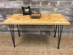 Sleek and sturdy, this table offers a simple and appealing look to add to any space. The light walnut color combines wonderfully with the black iron hairpin legs for those looking for a softer industrial feel.  The table top is created using repurposed wood fixture shelving that was saved from the closing of a local home goods retailer here in the Dallas/Fort Worth area. A border of select pine is added to finish off the simple design and it is then thoroughly sanded and rubbed with Danish…