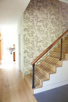 modern staircase by Actual Size Projects. Chunky wood railing at the top of cable rails. Warms things up.
