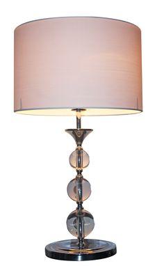 Piękna lampa stołowa Zuma Line Rea z tkaninowym kloszem w kolorze białym oraz korpusem wykonanym ze szklanych kul. Lampa z pewnością będzie interesującym dodatkiem w każdym salonie i sypialni. Jej niepowtarzalne wzornictwo przyciąga wzrok i nadaje wnętrzu stylowy charakter.