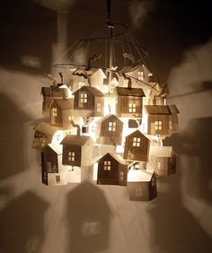 hutch studio: Light comprised of 33 paper houses made from vintage 50's cookbook pages.  They hang with thread from a spiraling wire support.