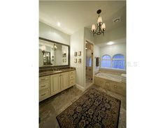 Light blue walls, black accents, antique white cabinets metallic mirrors