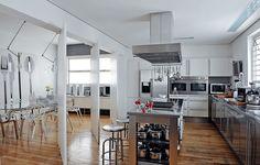 A cozinha tem a linguagem da arquiteta Valéria Blay, que gosta da neutralidade do branco, do preto e do prata. A sala de jantar pode ser isolada com portas pivotantes. Para facilitar, as panelas ficam em prateleiras abertas na ilha