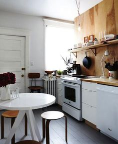 tripod table (west elm) in small kitchen with plywood walls