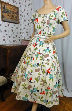 Cherry and birds novelty print cotton dress. Summertime fun in the sun dress. - short cap sleeves - side metal zipper - pinked seams - wide scoop neck with scallop edging - AB rhinestones, studs and teardrop bead trim at the neck - belt loops - full gathered skirt - neckline and sleeves are lined with olive green cotton - back oversize self fabric bow with green lining - green panel in the gathered on skirt - print has red cherries, aqua and tan blossoms and birds plus green leaves and black…