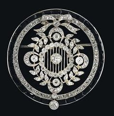 Cartier – An art nouveau brooch  platinum 950, old-cut brilliants, -diamonds, and diamond rhombs, total weight ca. 1,60 ct, onyx of baguette-cut, moving central segment, signed Cartier Paris London New York No. 7896, French hallmark, workmanship ca. 1910/20, 10,6 g, small brooch elements of white gold, with case