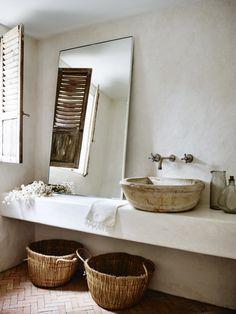 Quelques pistes pour adopter une salle de bain wabi sabi    Réalisation CM studio // Une salle de bains de style wabi sabi très réussie avec son évier en pierre et son sol en brique. J'adore le miroir vintage, les paniers ethniques.
