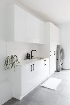 Large and contemporary white laundry with grey floor tile. Modern and streamlined laundry with black handles and accessories. White Laundry Rooms, Modern Laundry Rooms, Laundry In Bathroom, Laundry Nook, Laundry Decor, Laundry Closet, Laundry Room Inspiration, Laundry Room Organization, Grey Bathrooms