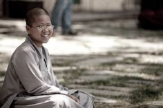 a Buddhist nun in the Dalai Lamas residence monastery in Dharamasala, India. Taking part in a debating session. When the monk has made their point they slap their hands together and wait for their opponents rebuttal.  http://scottellison.net/blog/2014/4/23/travel-portrait-photography-buddhist-nun-dharamasala-india