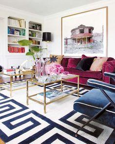 Blue velvet chair, fuschia sofa, built-0in shelves and white rug with blue Greek key pattern