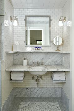 Cottage bathroom nook is filled with cream mini subway tiles lined with a wall-mount gray marble washstand with mini marble shelves under inset framed medicine cabinets illuminated by white glass sconces atop a white mosaic marble brick tiled floor finished with a gray mosaic marble border.