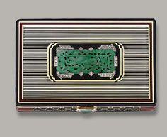 AN ART DECO JADE, ENAMEL AND DIAMOND VANITY CASE, BY CARTIER The dark blue enamel striped case with red border to the central jade carved panel depicting a figure of Buddha with diamond-set foliate borders and clasp of similar design, opening to reveal a mirror ,lipstick holder and powder case, circa 1925