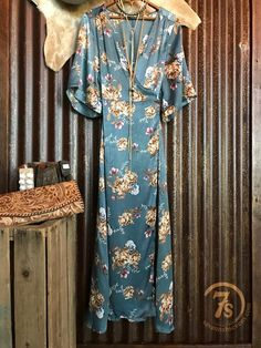 "The Skye - Dusty blue floral dress.Retro print and satin feel. Cross over wrap style. Can be tied on side or back. V-neck.Wide sleeve. Vintage style cut. Length hits right above the ankle on a 5'6"" woman."