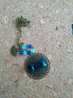 Collana lunga in bronzo e fiocco blu in fimo.