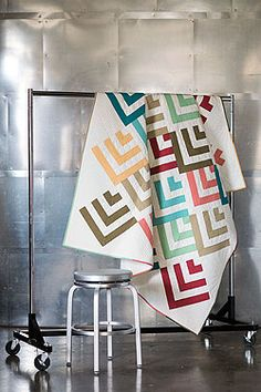 """Mod Cabin Fon's and Porter's Easy Quilts Summer 2014 This full-size quilt features a variation on the classic log cabin block. The colorful pieced strips are arranged to create a chevron design. Finished Size: 72"""" × 89"""" Finished Blocks: 32 (12"""") blocks Rating: Easy"""