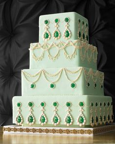 """Bejeweled Wedding Cake with Opulent Jewels.  No wonder King George went mad! He was likely driven to distraction by the opulent jewelry Englishwomen took to wearing during the 18th and early 19th centuries. This cake is a homage to those showstoppers, with four regal tiers of spearmint-hued fondant, royal icing piped to mimic pearl strands, and sparkling edible baubles, each ringed in a """"pave setting"""" of royal-icing pearls."""
