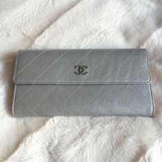"""NWOT Chanel wallet / clutch in silver leather CHANEL stunning silver quilted lambskin leather flap wallet! NWOT, limited edition. Can also be used as a clutch - easily fits my IPhone inside. Features light pink leather side trim and detailed silver CC logo snap closure. Inside wallet has 12 card holders, zip middle pocket and multiple billfold sections. 7.5""""W x 4""""H x 1.5""""D. Bundle discount does not apply to this item. Authenticity card, box and dust cloth all included! 💝🛍💝 CHANEL Bags…"""