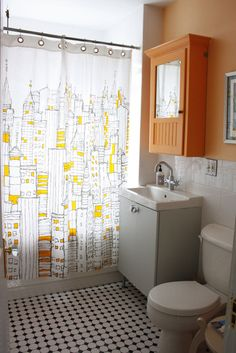 traditional elements (black and white tile on the floor, square tile on the wall) with a punch of orange and modern sink and shower curtain #orange