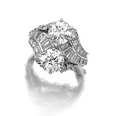 DIAMOND RING, KERN. Of cross over design, set with two circular-cut diamonds bordered by square-, single-cut and baguette stones, mounted in platinum, signed Kern. [Interesting use of baguettes and rounds as well as the crossover style]