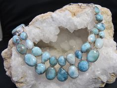 """Hand-polished Caribbean Larimar necklace with hand-selected gemstones in oval, round and teardrop shapes, set in 925-hallmarked sterling silver. Length: 16-22""""+ Adjustable toggle clasp. Largest center"""