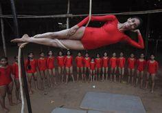 Una niña practica 'mallakhamb', un antiguo deporte indio, sujeta a una cuerda, en Mumbai