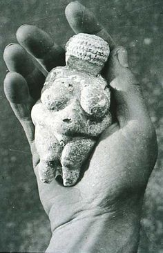 """Venus of Willendorf"" on hand - most important mother goddess statuette, circa 24,000-22,000 BCE, made in limestone, high 11cm - at the Naturhistorisches Museum, Vienna"