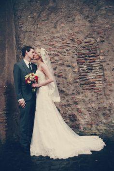 Winter destination wedding in Rome, Italy. Dress: Emma by Maggie Sottero. #mantillaveil #mantilla #lacegown #lace #greysuit #rome #italy #wedding #winterwedding #bouquet #roses #ranunculus #vintage #weddingphoto  #kiss #weddingdress #dress #groom #bride #bridal #bridalhair #veil #mantilla #destinationwedding #maggiesottero