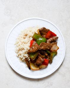 "Chili Garlic Beef Stir Fry with Coconut Jasmine Rice 1 1/2 pounds thinly sliced beef (I find mine at whole foods, labeled ""stir fry beef"") 1 teaspoon salt 1 teaspoon pepper 1/4 cup olive oil 3 tablespoons brown sugar 1 chipotle pepper in adobo sauce, diced 2 teaspoons adobo sauce from the can of chipotles in adobo 4 garlic cloves, minced 2 tablespoons coconut oil 1 green bell pepper, chopped 1 red bell pepper, chopped 1 sweet onion, sliced"