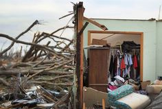 Clothes hang untouched in a closet inside a destroyed house in Joplin, Mo. on May 23.