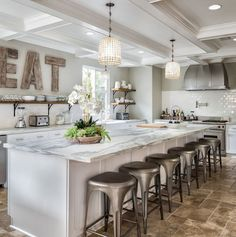 Kitchen features a long island with white and gray marble countertop. Kitchen with long island. #KitchenLongIsland #Longislandcountertop SoCal Property Portraits.