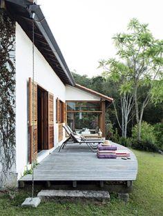 O trecho do telhado acima do novo deck ganhou uma calha de cobre que ajuda o beiral de 60 cm a proteger as portas dos quartos das chuvas comuns no verão. A distância de 60 cm do solo evita umidade.