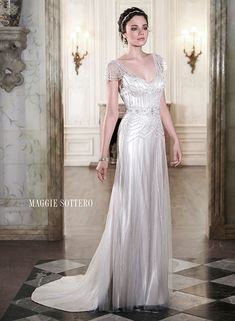 Tulle and satin sheath dress adorned with sparkling Swarovski crystals and pearl beads. Finished with illusion cap-sleeves, Ettia by Maggie Sottero.
