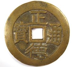 """This is the obverse side of the charm. The inscription is zheng de tong bao (正德通宝).This is a popular legend for charms because zheng de has the auspicious meaning of """"correct virtue"""" in Chinese which is an appropriate wish for a newlywed couple.Additional details concerning this charm can be found at Chinese Charms with Coin Inscriptions.The charm has a diameter of 45 mm and weighs 14.5 grams. The reverse side of the charm has a very detailed dragon and phoenix symbolizing the marriage…"""