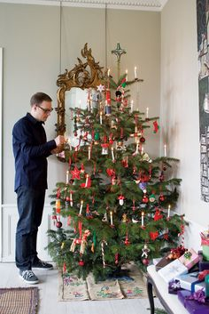Is he lighting candles on the tree...? That was the way once upon a time. A bit risky nowadays. Beautiful tree.
