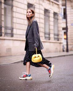 10 looks com o tênis que está dominando o street style. Blazer cinza xadrez oversized, vestido preto de bolinhas, tênis esportivo, balenciaga ulgy dad shoes