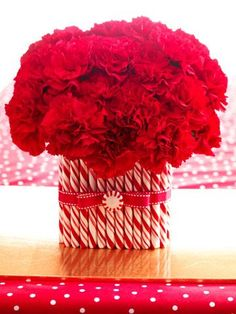 wrap a vase in peppermint sticks and pair with red flowers for a pretty Christmas decoration