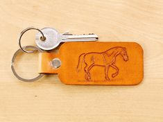 This completely unique Horse keychain is hand carved from premium quality leather and has a hand carved strolling horse. Click To Shop Now. The hand carved leather keychain is hand dyed brown on the front and on the reverse.This beautiful tooled leather key fob could be given as a 3rd leather anniversary gift to husband, or perhaps as a gift for mom or any horse lover. #handmade #horse #horsegift #leatherkeyring #leatherkeyfob #leatherkeychain #leatheranniversary Leather Bookmark, Leather Keyring, Leather Gifts, Leather Tooling, Leather Craft, Tooled Leather, Leather Anniversary Gift, 3rd Anniversary Gifts, Horse Gifts