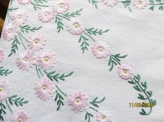 Perfect for an afternoon tea. Gorgeous creamy white linen tablecloth with pink daisies and green foliage in each corner. Swags of smaller flowers connecting the corner patterns. Softer pinks and greens in a center circle. Pin hole edging.  Remember this table cloth was probably done as a hobby and by a home maker so all hand made, This table cloth was clearly done by a perfectionist  Excellent vintage condition- Has clearly been cared for. Colours bright Embroidery excellent top and…